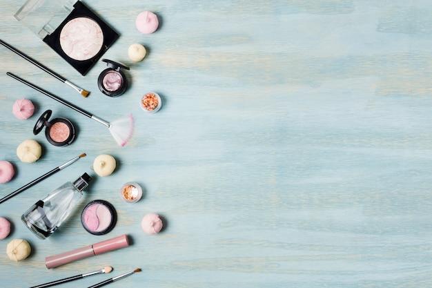 Escovas de sombra e cosméticos ao lado de doces Foto gratuita