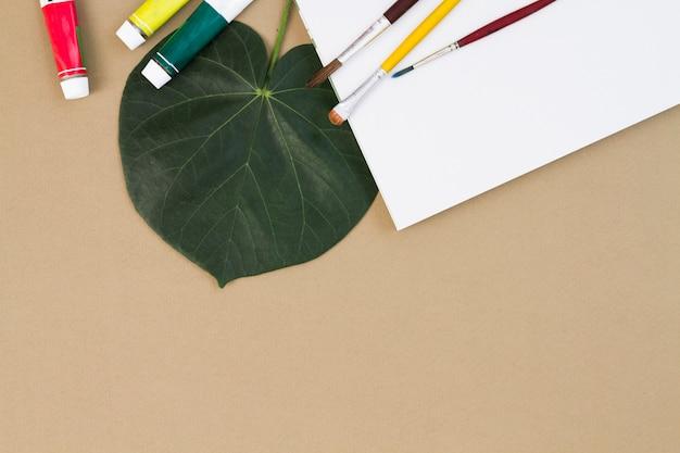 Escovas e tintas espalhadas na folha de papel Foto gratuita