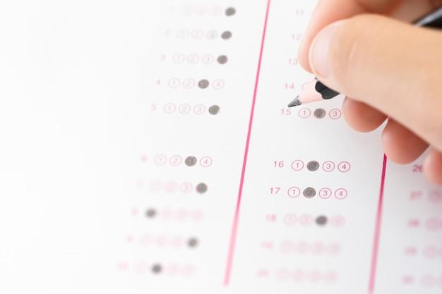 Escreva na mão o estudante para escrever a resposta da pergunta do exame de teste Foto Premium