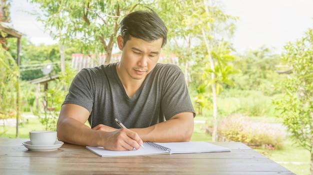 Escrita asiática do homem em um caderno em um café. Foto Premium