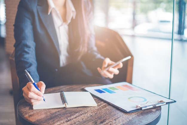 Escrita da mão da mulher de negócio em um bloco de notas com uma pena e utilização do smartphone no escritório. Foto Premium