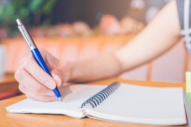 Escrita da mão da mulher em um bloco de notas com uma pena no escritório. Foto Premium
