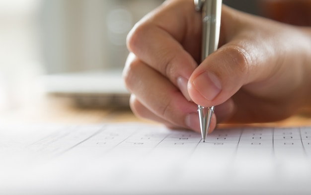 Escrita da mão em um papel com uma caneta Foto gratuita