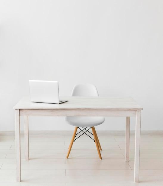 Escritório minimalista com mesa e laptop Foto gratuita