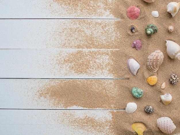 Escudo do mar com areia em fundo de madeira. vista superior com espaço de cópia. viajar férias de verão. Foto Premium