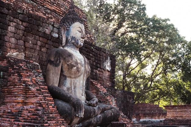 Escultura que está a imagem de buddha de wat mahathat no parque nacional de sukhothai em tailândia no por do sol. Foto Premium