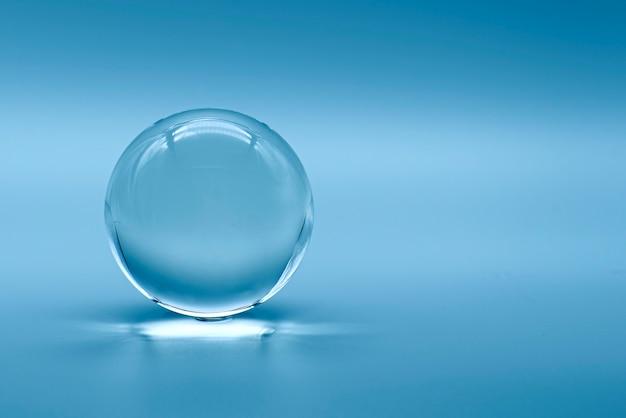 Esfera de vidro em fundo azul Foto Premium
