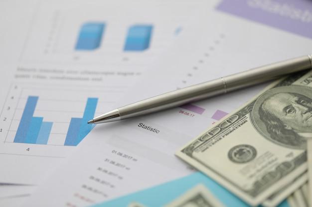 Esferográfica de prata mentira em dinheiro dólar com negócios Foto Premium