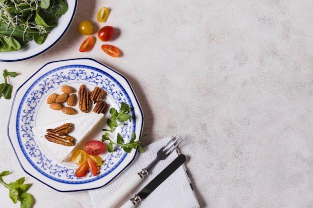 Esfolar a configuração do prato com nozes e salada Foto gratuita