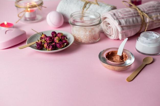 Esfoliação caseira e cuidados com a pele com ingredientes orgânicos naturais em fundo rosa com toalhas, velas e sabão Foto Premium
