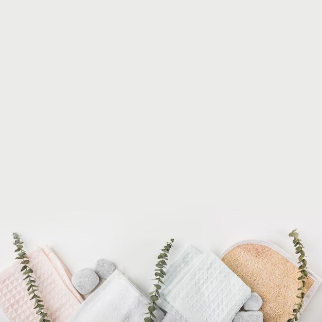 Esfoliação corporal de bucha; guardanapo de algodão e pedras spa com galhos em fundo branco Foto gratuita