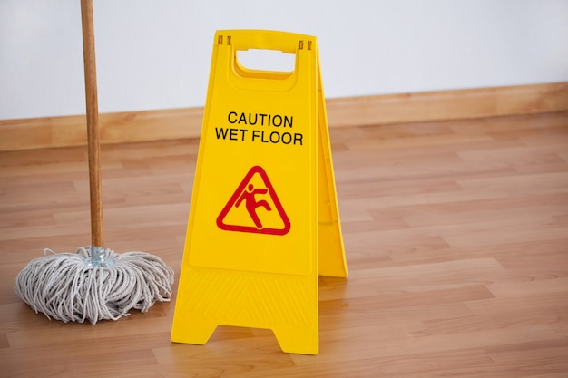 Esfregão com sinal de cuidado de piso molhado Foto Premium