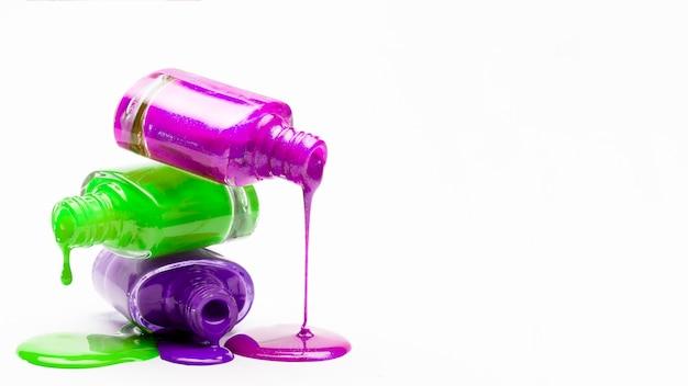 Esmalte pingando de garrafas empilhadas contra o pano de fundo branco Foto gratuita
