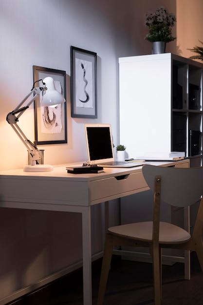 Espaço de trabalho agradável e organizado com lâmpada Foto gratuita