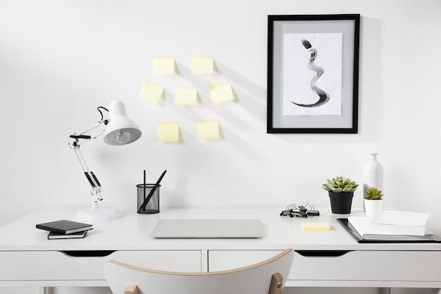 Espaço de trabalho arrumado e organizado com lâmpada na mesa Foto gratuita