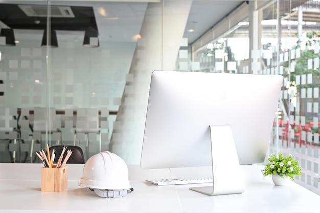 Espaço de trabalho com computador, capacete de segurança e lápis na mesa de escritório. Foto Premium