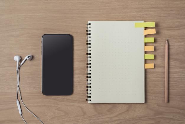 Espaço de trabalho com diário ou notebook e telefone inteligente, fone de ouvido, lápis, notas sobre madeira Foto Premium