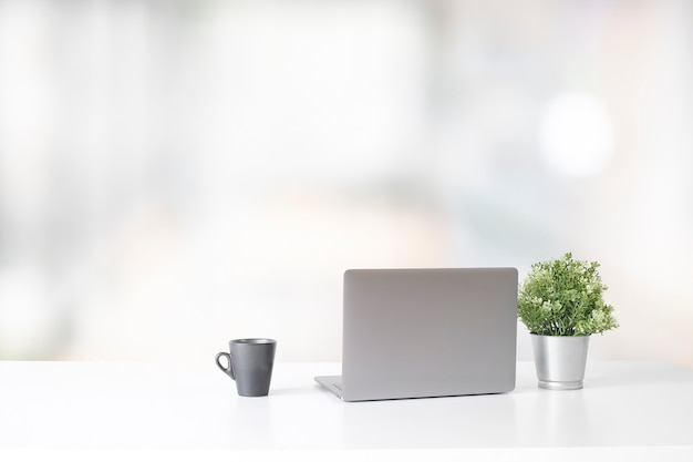 Espaço de trabalho com o computador portátil e o copo e a planta de café, conceito à moda do trabalho de mesa do escritório. Foto Premium