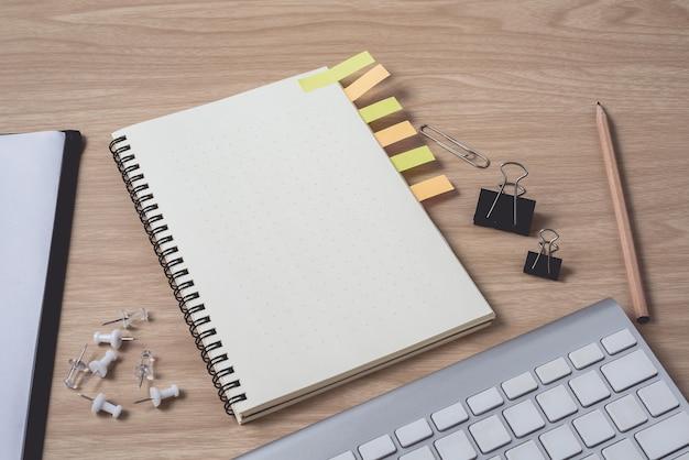 Espaço de trabalho com o diário ou notebook e prancheta, teclado, lápis, notas autoadesivas Foto Premium