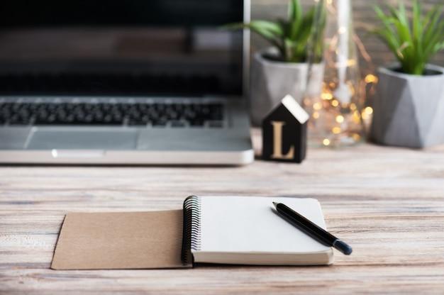 Espaço de trabalho com o diário vazio, laptop Foto Premium