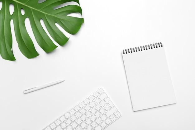 Espaço de trabalho com teclado, folha de palmeira e acessórios. vista plana, espaço de cópia de vista superior Foto Premium