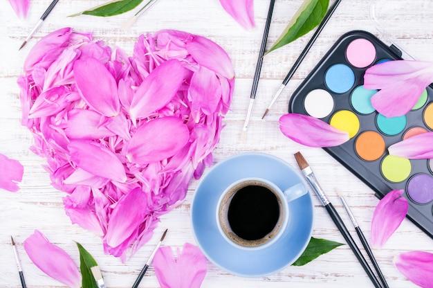 Espaço de trabalho com uma xícara de café e flores Foto Premium