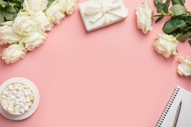 Espaço de trabalho de mulher com rosas brancas, presente, café, bloco de notas, caneta na rosa. vista superior com espaço de cópia. Foto Premium