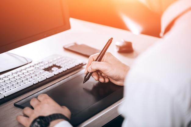 Espaço de trabalho do designer gráfico. mão no tablet pen. homem no escritório. Foto Premium