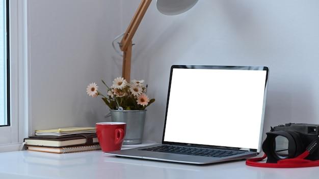 Espaço de trabalho do fotógrafo ou designer com laptop de tela em branco branca e equipamentos na mesa branca. Foto Premium