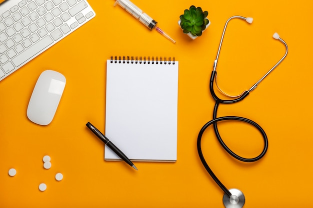 Espaço de trabalho do médico com equipamentos médicos na mesa amarela Foto Premium