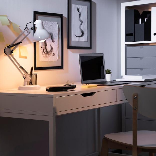 Espaço de trabalho limpo e arrumado com laptop e lâmpada Foto gratuita