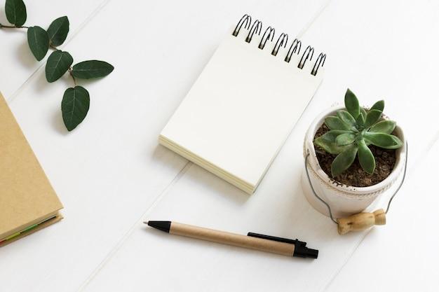 Espaço de trabalho minimalista com o bloco de notas e caneta e vaso de planta de casa Foto gratuita