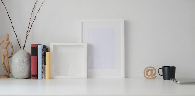 Espaço de trabalho mínimo com moldura em branco e material de escritório, mesa de madeira branca Foto Premium