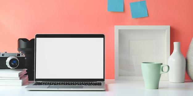 Espaço de trabalho mínimo com o computador portátil de tela em branco aberta Foto Premium