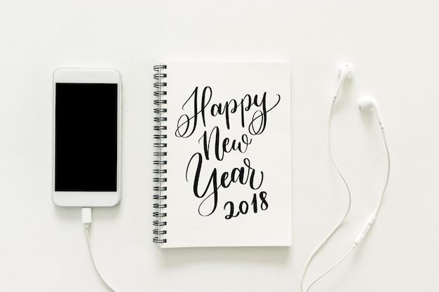 """Espaço de trabalho mínimo - Creative flat lay foto da mesa do espaço de trabalho com """"2018 Happy New Year"""" no caderno de cadernos e no telefone celular com tela em branco e fone de ouvido no fundo branco. Vista de cima, conceito de ano novo. Foto gratuita"""