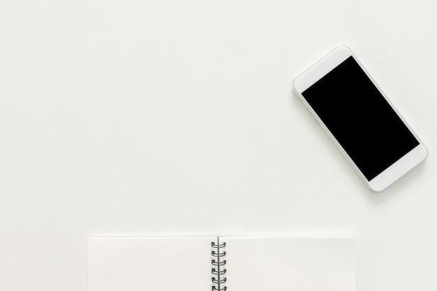 Espaço de trabalho mínimo - foto plana plana criativa da mesa do espaço de trabalho com bloco de desenho e telefone celular com tela em branco no espaço branco do espaço da cópia. vista de cima, fotografia de lay lay. Foto gratuita