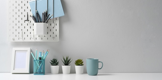 Espaço de trabalho moderno com moldura branca, papelaria, xícara de café e planta de casa em uma mesa bem organizada. Foto Premium