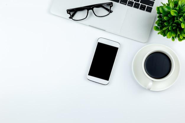 Espaço de trabalho no escritório com smartphone com telas vazias em branco estão no topo Foto Premium