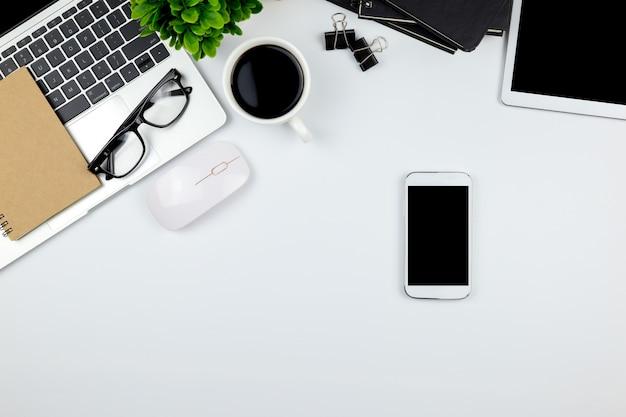 Espaço de trabalho no escritório com tablet e smartphone com telas vazias em branco. Foto Premium