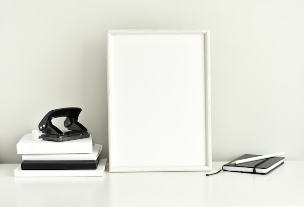 Espaço de trabalho preto e branco, moldura em branco, material de escritório. Foto Premium