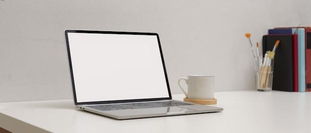 Espaço de trabalho simples com mock-se laptop, copo, cópia espaço pincéis de pintura e livros na mesa branca Foto Premium