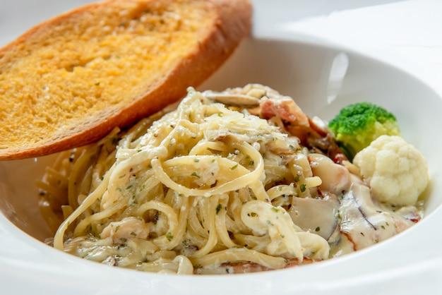 Espaguete à carbonara com baguete na chapa branca Foto Premium