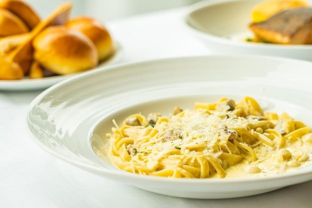 Espaguete amarelo carbonara com molho de creme branco no prato na mesa - comida italiana Foto gratuita
