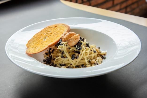Espaguete com baguete em chapa branca Foto Premium