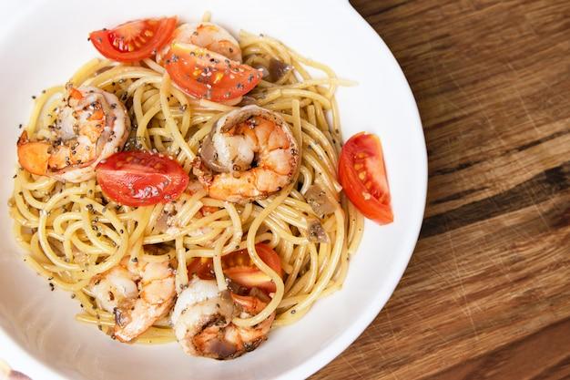 Espaguete com camarão frito e tomate fresco. Foto gratuita