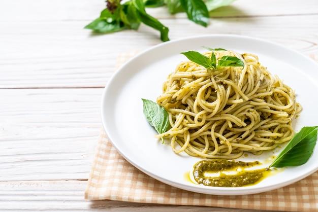 Espaguete com molho pesto, azeite e folhas de manjericão. Foto Premium