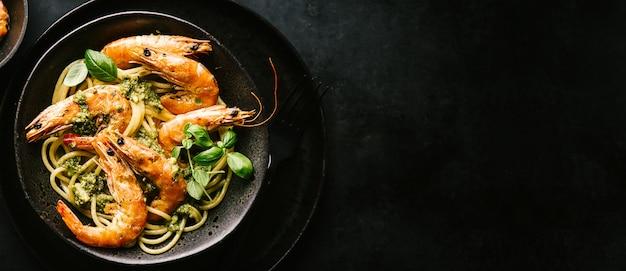 Espaguete com pesto e camarão servido na chapa Foto gratuita