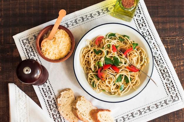 Espaguete com queijo ralado; pão e azeite no tapete branco Foto gratuita