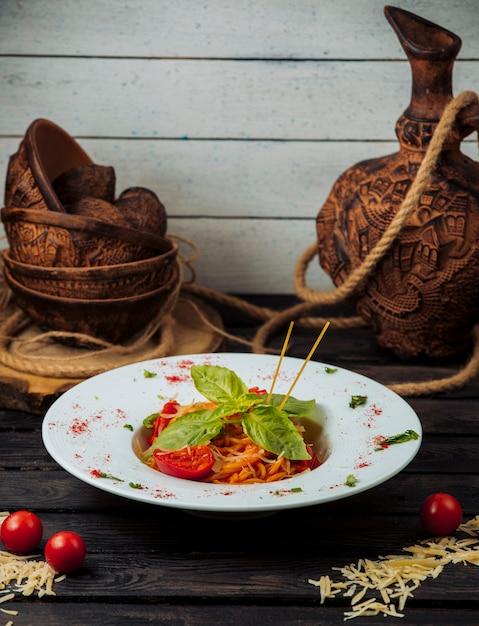Espaguete de tomate clássico decorado com parmesão ralado e manjericão fresco Foto gratuita