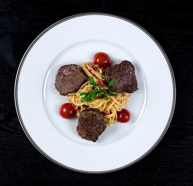 Espaguete em molho com rissóis de carne frita Foto gratuita